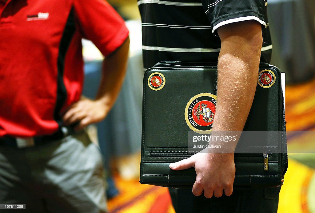 A job seeker holds a folder with US Marines stickers as he meets with a recruiter during the 'Hiring Our Heroes' job fair on April 30 2013 in Walnut...