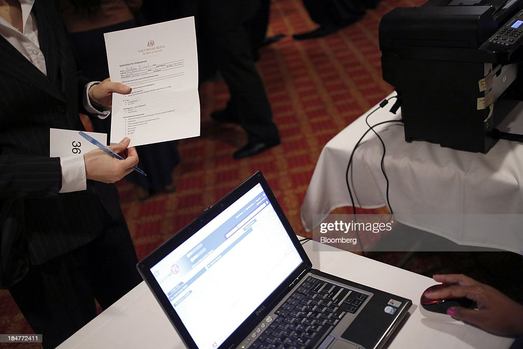 A job seeker holds an employment application during a job fair hosted by the Galt House Hotel in Louisville, Kentucky, U.S., on Monday, Oct. 14, 2013. Improvement in the U.S. labor market may soon speed up, building on gains during the past year, Federal Reserve researchers said, citing six employment indicators. Photographer: Luke Sharrett/Bloomberg via Getty Images