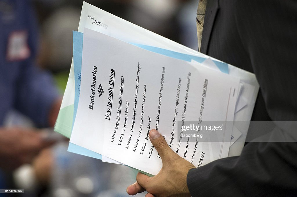 A job seeker holds Bank of America Corp. paperwork while talking with a recruiter at the Spring LGBT Career Fair in San Francisco, California, U.S., on Wednesday, April 24, 2013. Fewer Americans than forecast filed first-time claims for unemployment insurance payments last week, pointing to an improving labor market. Photographer: David Paul Morris/Bloomberg via Getty Images