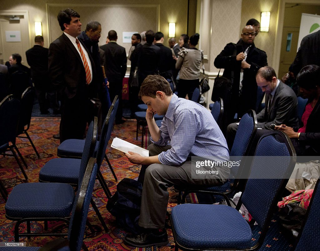 A job seeker looks over his resume before seeing recruiters at a job fair organized by United Career Fairs in New York, U.S., on Tuesday, Feb. 19, 2013. The U.S. Labor Department is scheduled to release initial jobless claims figures on Feb. 21. Photographer: Jin Lee/Bloomberg via Getty Images