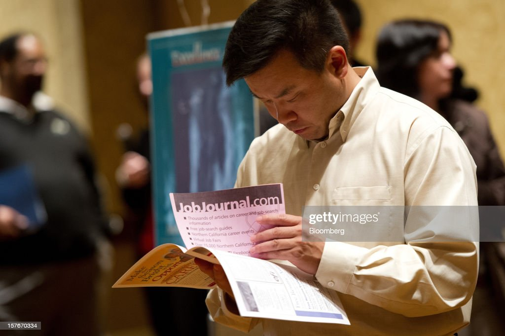 A job seeker looks over material during a HIREvent job fair in San Jose, California, U.S., on Tuesday, Dec. 4, 2012. The U.S. Labor Department is scheduled to release initial jobless claims data on Dec. 6. Photographer: David Paul Morris/Bloomberg via Getty Images