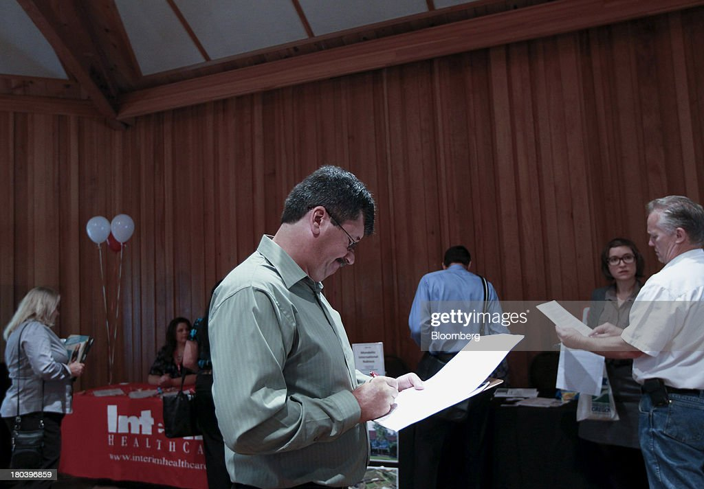A job seeker reads a prospectus at the annual Maximum Connections job fair in Portland, Oregon, U.S., on Thursday, Sept. 12, 2013. Jobless claims in the U.S. declined last week to the lowest level since April 2006 as work on computer systems in two states caused those employment agencies to report fewer applications. Photographer: Natalie Behring/Bloomberg via Getty Images