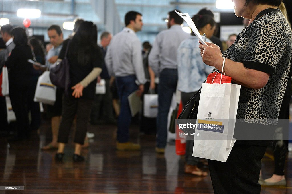 A job seeker reads an information sheet at a jobs and skills expo run by the Australian government in Melbourne, Australia, on Thursday, Oct. 4, 2012. Australia's unemployment rate probably climbed to 5.3 percent last month from 5.1 percent in August, according to the median estimate of economists surveyed by Bloomberg News. Photographer: Carla Gottgens/Bloomberg via Getty Images