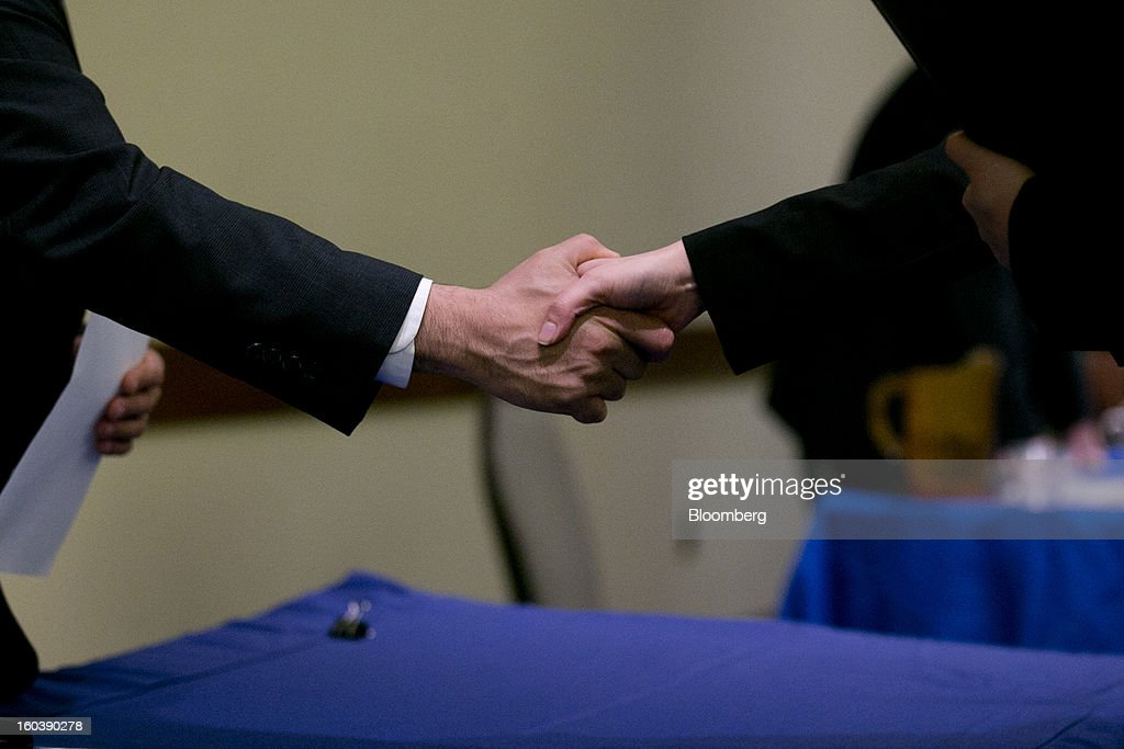 A job seeker, right, shakes hands with a job recruiter at a National Career Fairs job fair in Arlington, Virginia, U.S., on Wednesday, Jan. 30, 2013. The U.S. Labor Department is scheduled to release initial jobless claims data on Jan. 31. Photographer: Andrew Harrer/Bloomberg via Getty Images