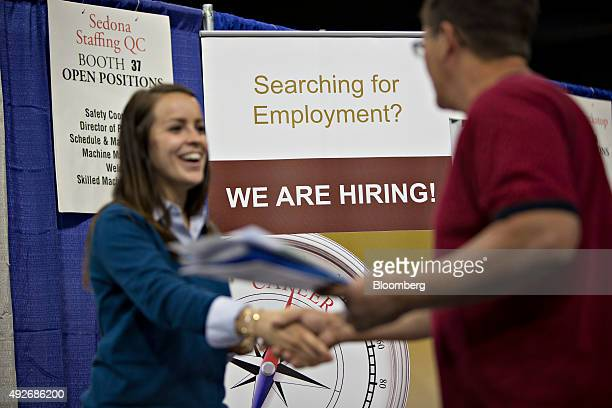 A job seeker right shakes the hand of a recruiter during the Quad Cities career fair in Moline Illinois US on Wednesday Oct 14 2015 The US Department...