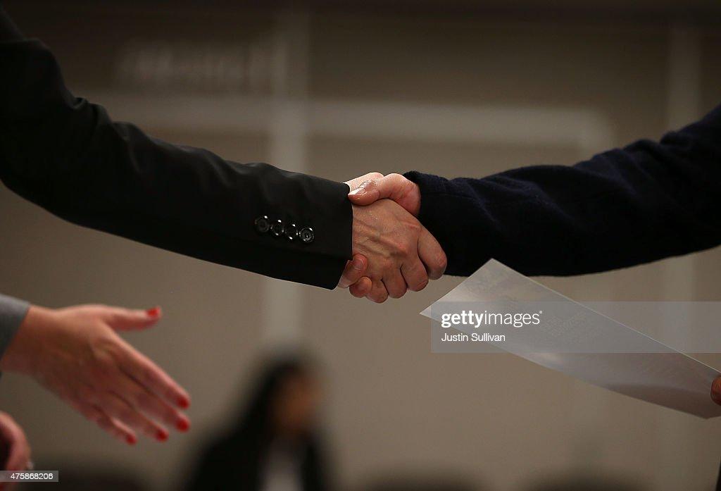A job seeker shakes hands with a recruiter during a HireLive career fair on June 4 2015 in San Francisco California According to a report by payroll...