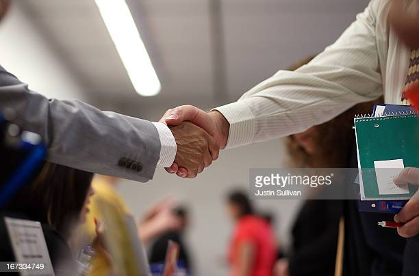 A job seeker shakes hands with a recruiter for the Fremont Unified School District during a job fair at the Alameda County Office of Education on...