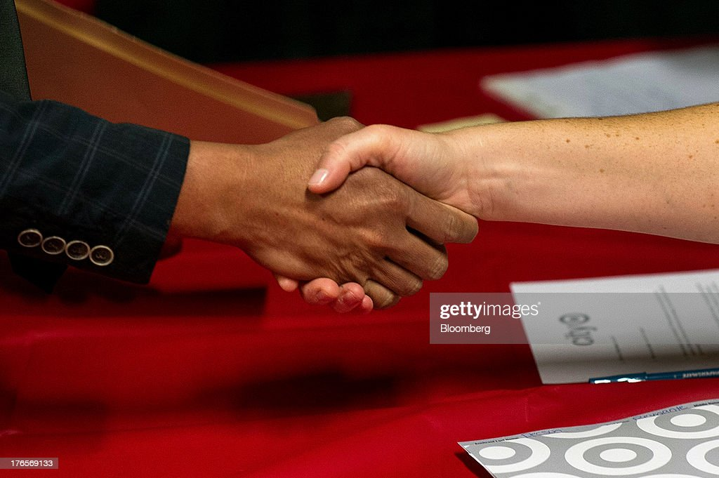 A job seeker shakes hands with a Target Corp. employee during a hiring event at a new store in San Francisco, California, U.S., on Thursday, Aug. 15, 2013. Claims for jobless benefits unexpectedly dropped by 15,000 to 320,000 in the week ended Aug. 10, the fewest since October 2007. Photographer: David Paul Morris/Bloomberg via Getty Images