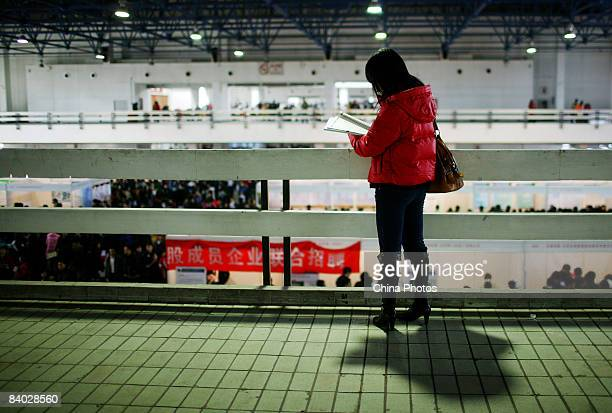 A job seeker views job informations at a job fair for postgraduate students on December 14 2008 in Beijing China Nearly 40000 applicants competed for...