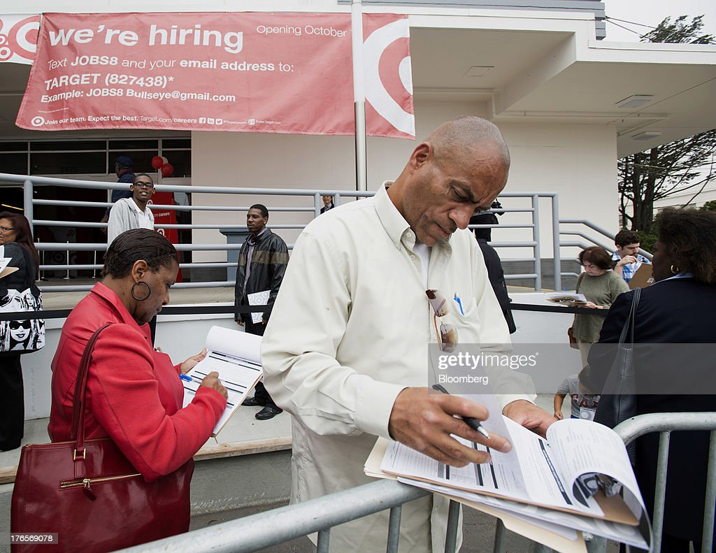 Job seekers fill out applications while waiting in line for a hiring event at a new Target Corp. store in San Francisco, California, U.S., on Thursday, Aug. 15, 2013. Claims for jobless benefits unexpectedly dropped by 15,000 to 320,000 in the week ended Aug. 10, the fewest since October 2007. Photographer: David Paul Morris/Bloomberg via Getty Images