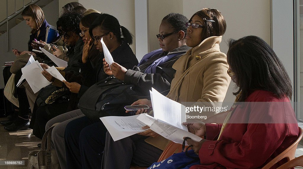 Job seekers look over resumes and paperwork before visiting booths at the City of Chicago job fair at Kennedy King College in Chicago, Illinois, U.S., on Friday, Nov. 9, 2012. The U.S. Department of Labor is scheduled to release initial jobless claims data on Nov. 15. Photographer: Frank Polich/Bloomberg via Getty Images