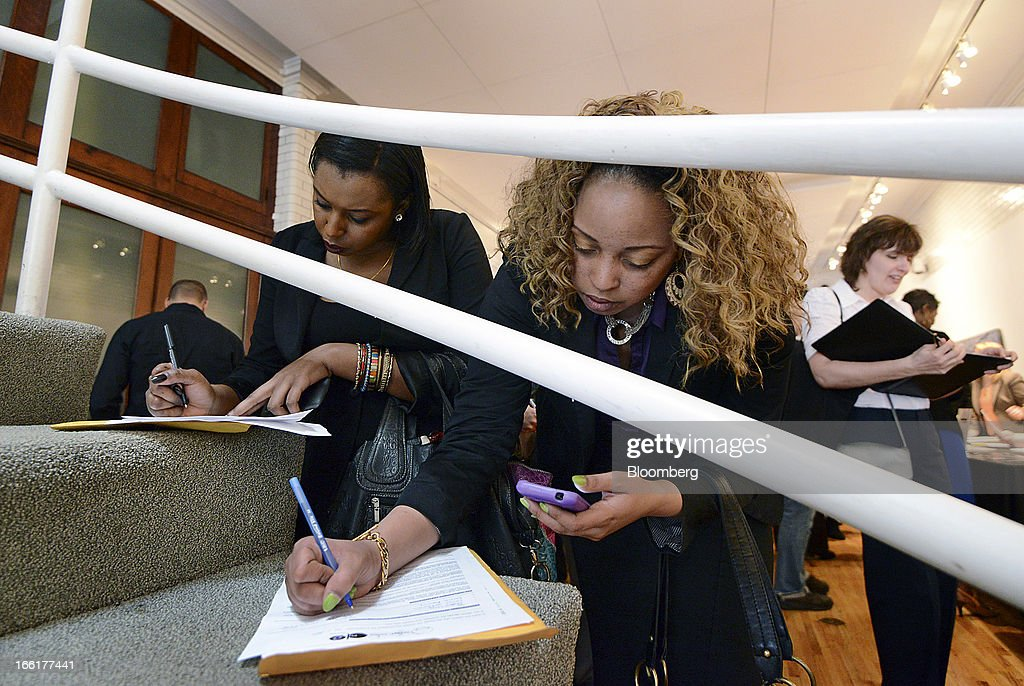 Job seekers Lovesha Johnson, center, and Charlene Sales, left, fill out a job applications during the NYC Restaurant Job Expo at the Gabarron Foundation in New York, U.S., on Tuesday, April 9, 2013. The U.S. Department of Labor is scheduled to release jobless claims figures on April 11. Photographer: Peter Foley/Bloomberg via Getty Images