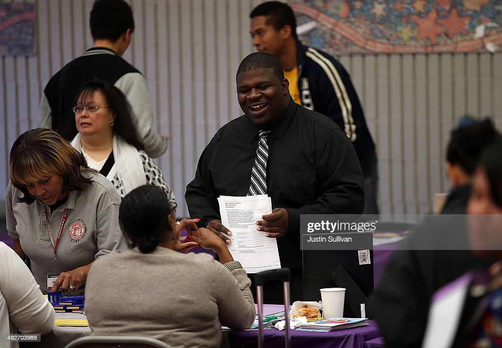 Job seekers meet with a recruiter during a career fair at the Southeast Community Facility Commission on May 21 2014 in San Francisco California Job...