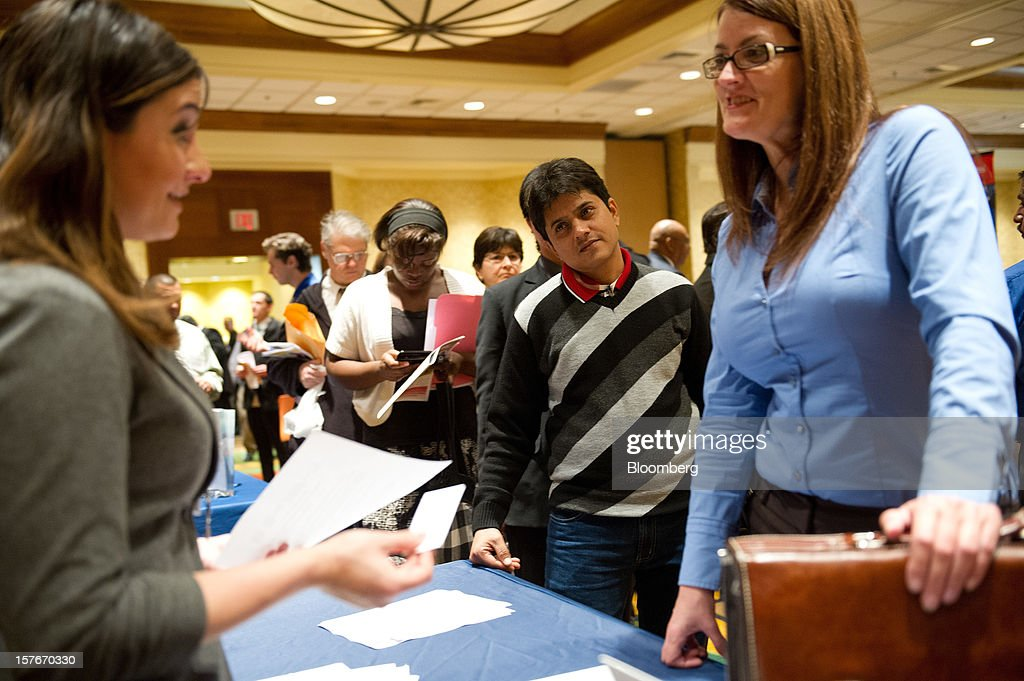 Job seekers speak with Sabrina Grech, staffing supervisor at Nelson Staffing Solutions, left, during a HIREvent job fair in San Jose, California, U.S., on Tuesday, Dec. 4, 2012. The U.S. Labor Department is scheduled to release initial jobless claims data on Dec. 6. Photographer: David Paul Morris/Bloomberg via Getty Images