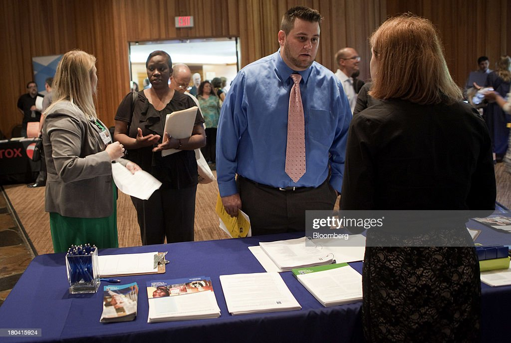 A job seekers speaks to a representative at the annual Maximum Connections job fair in Portland, Oregon, U.S., on Thursday, Sept. 12, 2013. Jobless claims in the U.S. declined last week to the lowest level since April 2006 as work on computer systems in two states caused those employment agencies to report fewer applications. Photographer: Natalie Behring/Bloomberg via Getty Images