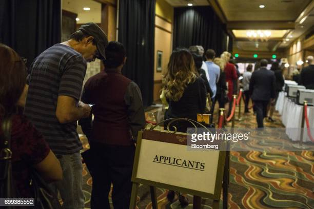 Job seekers stand on line to register for an interview time slot during a career fair at the Pechanga Resort and Casino in Temecula California US on...