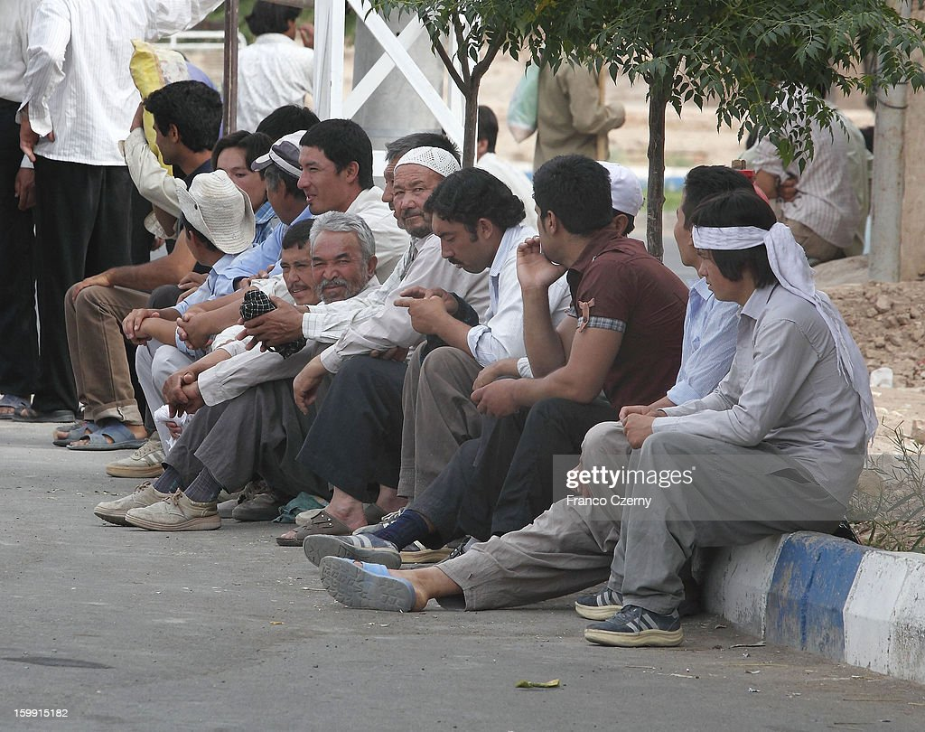 Job seekers wait for work early morning on August 15, 2012 in Aran, Iran.