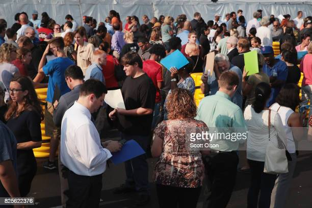 Job seekers wait in line to apply for 1 of the 2500 jobs being offered at the Amazon fulfillment center on August 2 2017 in Romeoville Illinois...