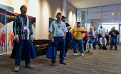 Job seekers wait in line to enter the Eagle Ford Shale Job Fair at the American Bank Center in Corpus Christi Texas US on Wednesday Oct 29 2014 The...