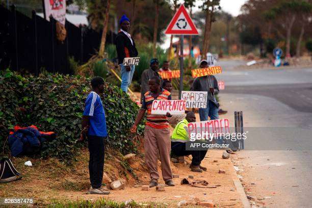 Job seekers wait on the side of a road holding placards reading their specialisation on August 4 2017 in Johannesburg South Africa Africa's most...