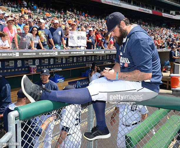 Joba Chamberlain of the Detroit Tigers autographs a baseball for a fan prior to the game against the Seattle Mariners at Comerica Park on August 17...