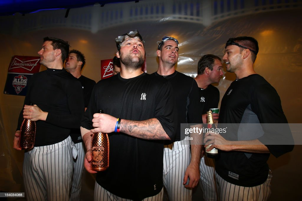 Joba Chamberlain #62 of the New York Yankees celerbrate in the locker room with his team after defeating the Baltimore Orioles by a score of 3-1 to win Game Five of the American League Division Series at Yankee Stadium on October 12, 2012 in New York, New York.