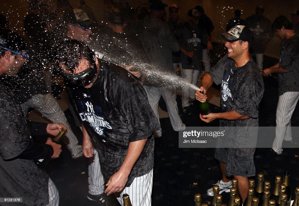 Joba Chamberlain of the New York Yankees is sprayed with champagne as he celebrates in the clubhouse after his team defeated the Boston Red Sox on...