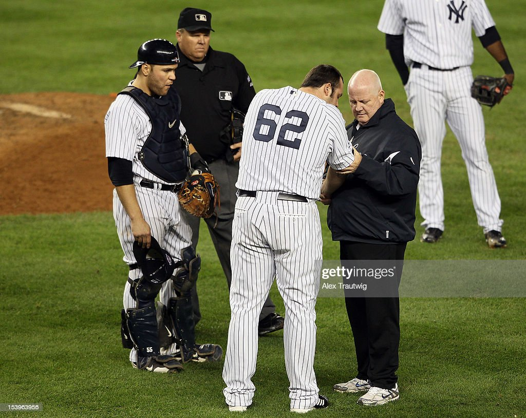 <a gi-track='captionPersonalityLinkClicked' href=/galleries/search?phrase=Joba+Chamberlain&family=editorial&specificpeople=4391682 ng-click='$event.stopPropagation()'>Joba Chamberlain</a> #62 of the New York Yankees receives medical attention after being hit by a broken bat during Game Four of the American League Division Series against the Baltimore Orioles at Yankee Stadium on October 11, 2012 in the Bronx borough of New York City.
