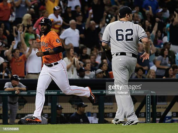Joba Chamberlain of the New York Yankees watches as Chris Carter of the Houston Astros scores a run in the seventh inning at Minute Maid Park on...