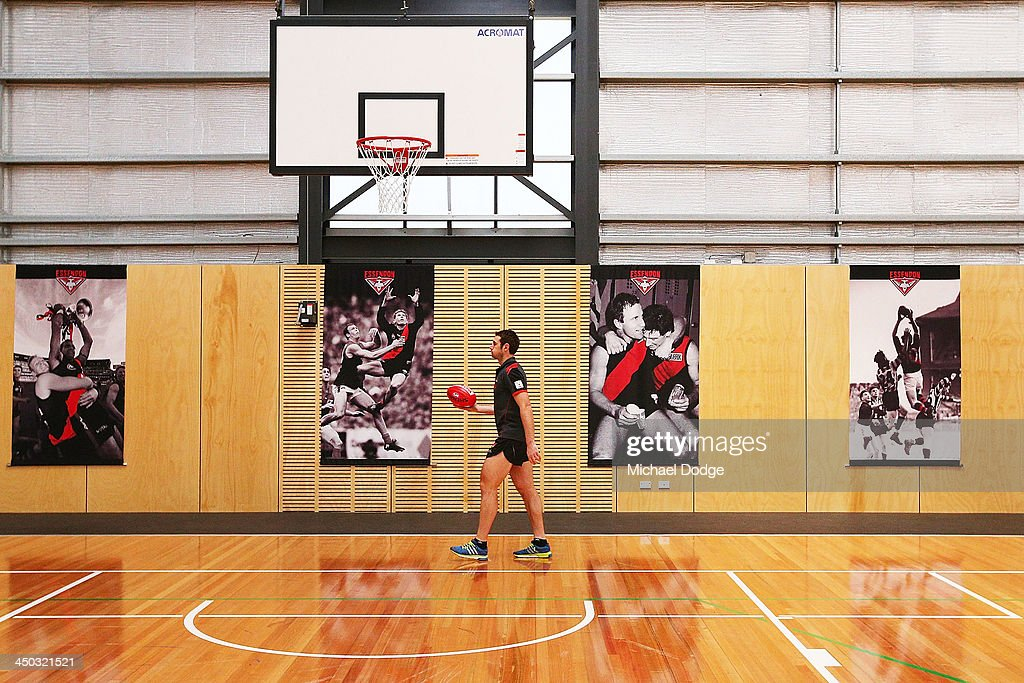 Jobe Watson is seen walking on the basketball court past a picture of his father Tim Watson at the new Essendon Bombers AFL training facility at Tullamarine on November 18, 2013 in Melbourne, Australia.