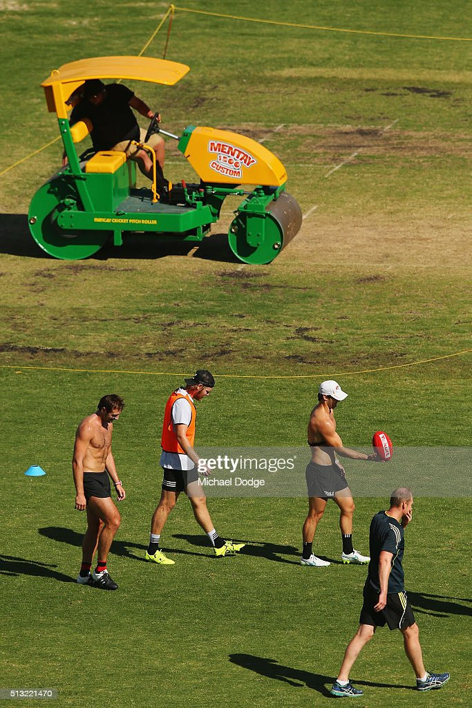 Jobe Watson Michael Hurley and Ben Howlett walk off as Sean Wellman monitors the players during a training session at StBernard's College on March 2...