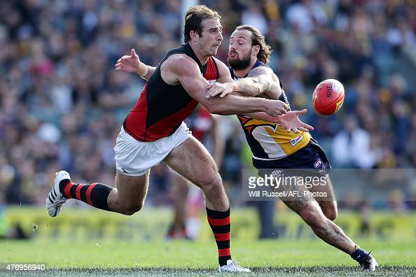 Jobe Watson of the Bombers handballs under pressure from Chris Masten of the Eagles during the round 11 AFL match between the West Coast Eagles and...