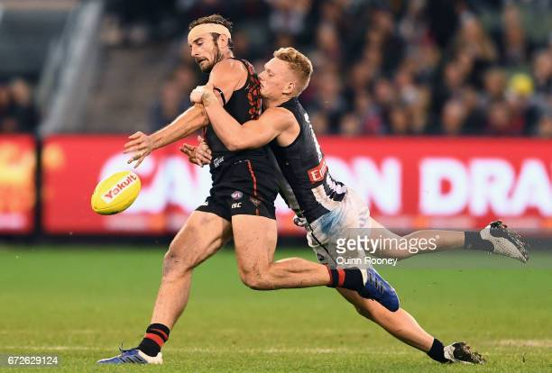 Jobe Watson of the Bombers kicks whilst being tackled by Adam Treloar of the Magpies during the round five AFL match between the Essendon Bombers and...