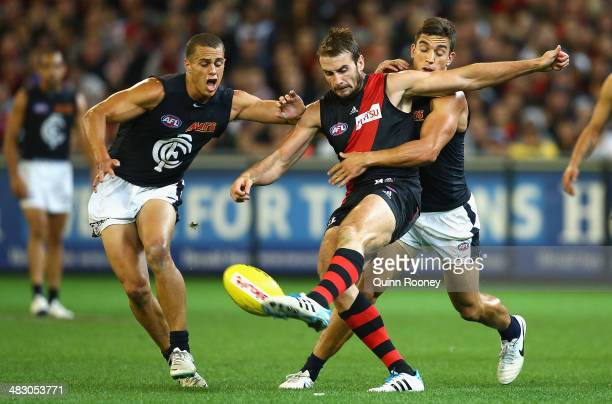 Jobe Watson of the Bombers kicks whilst being tackled by Andrew Carrazzo of the Blues during the round three AFL match between the Essendon Bombers...