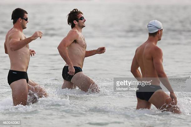 Jobe Watson runs out into the water with Brent Stanton and Jake Melksham during an Essendon Bombers AFL mini triathlon training session at...