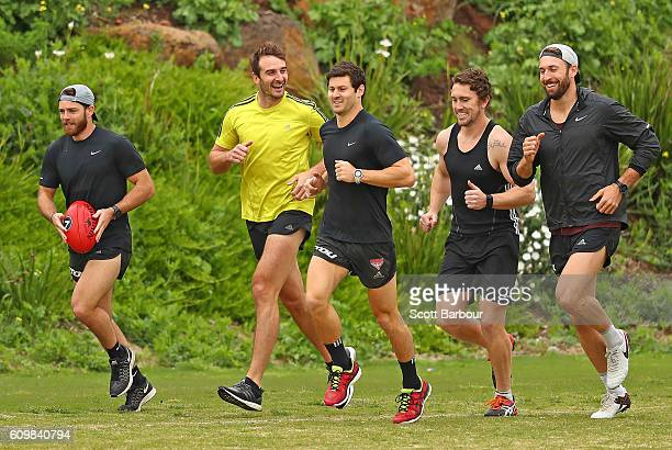 Jobe Watson smiles as he runs with his teammates after speaking to the media about his AFL playing future during an Essendon Bombers AFL media...