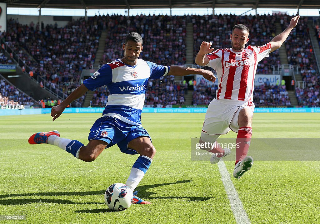Jobi McAnuff of Reading crosses as he is challenged by Marc Wilson of Stoke City during the Barclays Premier League match between Reading and Stoke City at Madejski Stadium on August 18, 2012 in Reading, England.