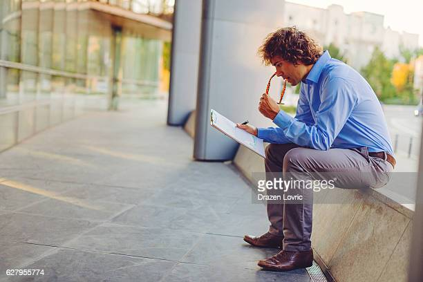 Jobless man filling application form for employment, near company headquarters