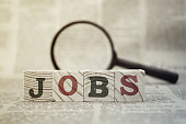 'Jobs' on wooden block and magnifying glass on newspaper background