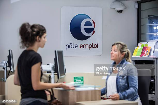 A jobseeker left speaks to an employee at a service counter inside a Pole Emploi job center the French national employment agency in Cahors France on...