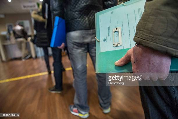 Jobseekers hold documents as they queue at service desks inside a Pole Emploi job center the French national employment agency in Montauban France on...