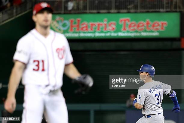 Joc Pederson of the Los Angeles Dodgers celebrates after hitting a solo home run in the seventh inning while Max Scherzer of the Washington Nationals...