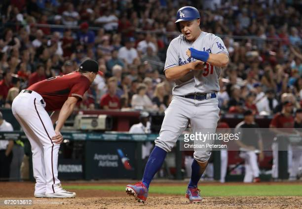 Joc Pederson of the Los Angeles Dodgers celebrates after scoring a run ahead of starting pitcher Shelby Miller of the Arizona Diamondbacks during the...