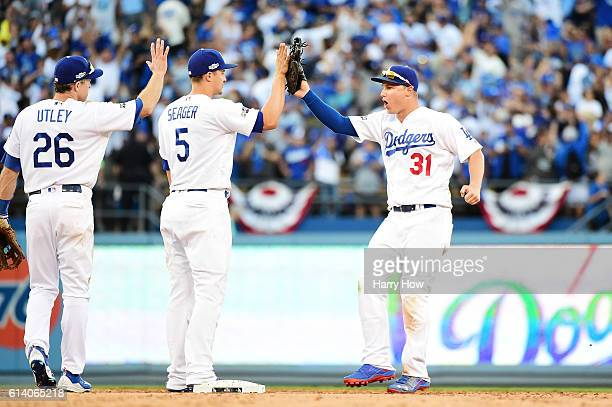 Joc Pederson of the Los Angeles Dodgers celebrates with Chase Utley and Corey Seager after their 6 to 5 victory over the Washington Nationals during...
