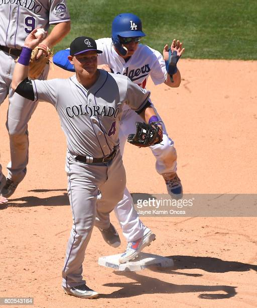 Joc Pederson of the Los Angeles Dodgers crashes into Pat Valaika of the Colorado Rockies and was called safe at second base in the game at Dodger...