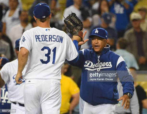Joc Pederson of the Los Angeles Dodgers gets a high five from manager Dave Roberts after the game against the Chicago White Sox at Dodger Stadium on...