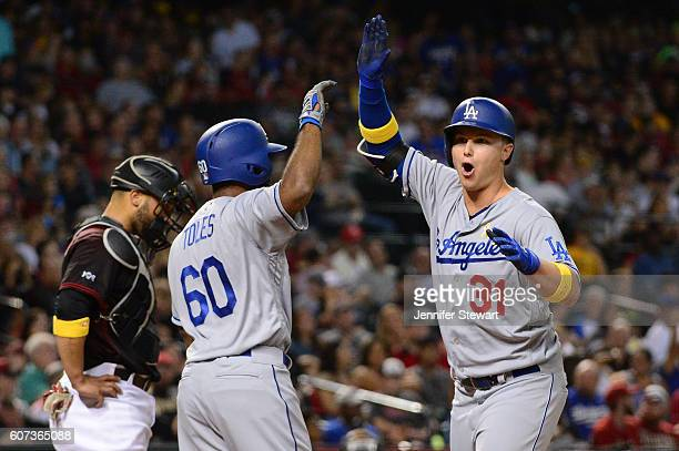Joc Pederson of the Los Angeles Dodgers is congratulated by teammate Andrew Toles after hitting a two run home run against the Arizona Diamondbacks...