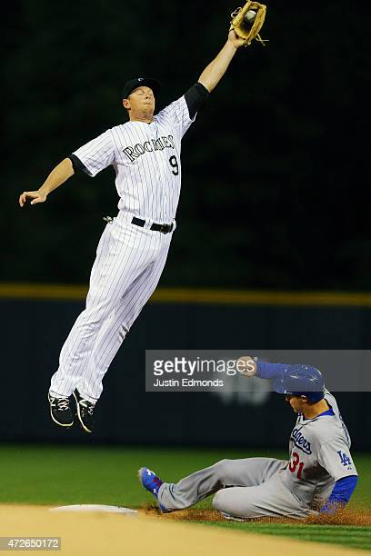 Joc Pederson of the Los Angeles Dodgers slides in for a stolen base as second baseman DJ LeMahieu of the Colorado Rockies has to jump to catch the...