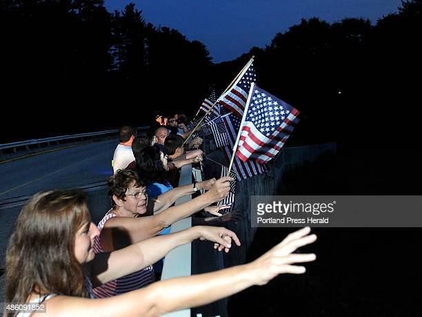Jocelyn Hanscom and her mother June Labbe join a crowd of well wishers who wave at honking horns while they wait for a procession with the body of...