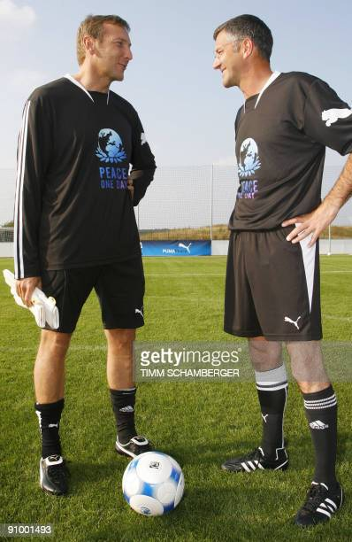 Jochen Zeitz chairman of German sports equipment manufacturer Puma and chairman of adidas AG Herbert Hainer prepare to play in a football match...